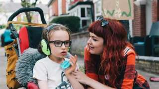 Mother Laura with her son Oscar. Oscar is in a wheelchair wearing ear defenders whilst his mum looks at him dotingly.