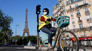 A woman cycles in Paris