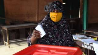 A voter casts her ballot at a polling station during the Benin Presidential election in Cotonou on April 11, 2021.