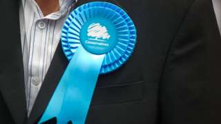 Man wearing Conservative party rosette