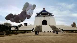 """在台北,透过手机程序可以看到在屏幕中虚拟出现的巨型吹气公仔""""Companion""""作品。"""