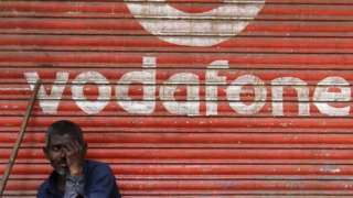 A man sits outside the downed shutters of a shop painted with a logo of Vodafone on its shutter in Mumbai, India on 24 February 2019