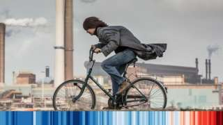woman on bike cycling past a factory