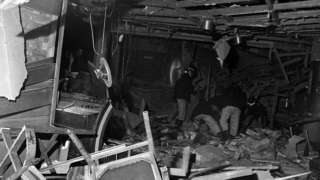 firemen search through the wreckage after a bomb went off in Birmingham