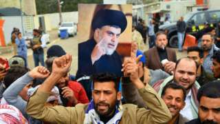 Supporter holds portrait of Moqtada al-Sadr, Najaf, Iraq (07/12/19)