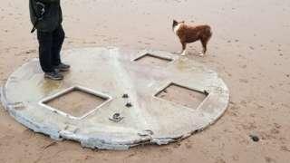Man and dog next to turbine part on beach