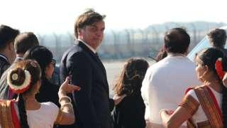 Em área aberta, Bolsonaro olha para trás em direção à câmera, enquanto é acompanhado por assessores e mulheres com trajes típicos na recepção ao presidente brasileiro