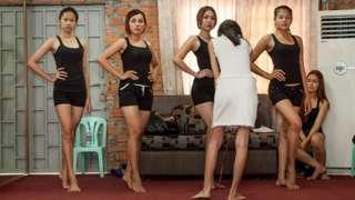 Perempuan Kamboja berpose dengan celana pendek dan kaos oblong.