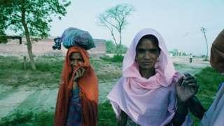 Duas mulheres Dalit com trajes típicos em terreno aparentemente baldio