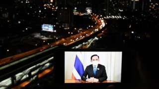 ภาพพล.อ. ประยุทธ์ จันทร์โอชา บนหน้าจอโทรศัพท์วางหน้ารถ ฉากหลังเป็นถนนในกรุงเทพฯ