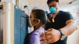Un médico realiza una placa de tórax a una niña en la clínica TB Móvil de Socios en Salud en Perú