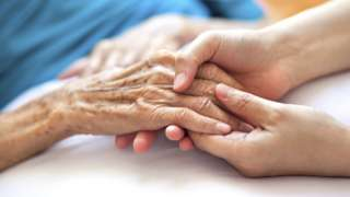 Close up of young woman's hand holding older lady's hand