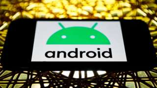 The Android logo on a phone screen in landscape mode, placed on an elaborate metal table lit in golden light