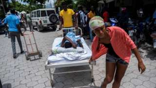 """A woman injured in Saturday""""s 7.2 magnitude quake is transported on a hospital bed to a hospital, in Les Cayes, Haiti August 16, 2021."""
