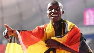 Joshua Cheptegei celebrates his world 10,000m title, draped in the Ugandan flag