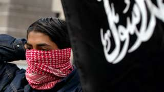 A boy ties on a scarf to hide his face August 25, 2002 during a 'Rally For Islam' demonstration held by al-Muhajiroun