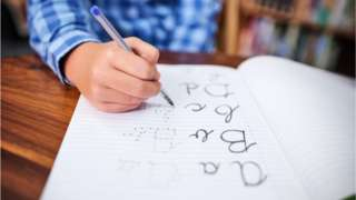 Boy's hand writing in exercise book