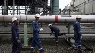 Workers next to a natural gas pipeline in Port Harcourt