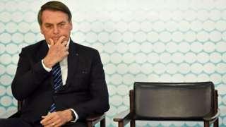 Bolsonaro sentado em cadeira durante evento olhando para baixo