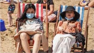 沙灘上的人們都戴著口罩