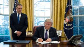 Robert Lighthizer watches as President Donald Trump signs a document in the Oval Office