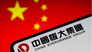设计图片:一台手机上显示着恒大集团标志,背景是中国国旗
