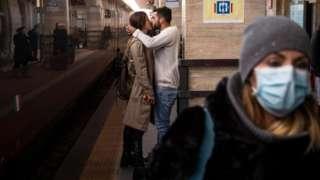 一对情侣在站台上拥吻