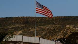 A U.S. flag is seen next to a section of the wall separating Mexico and the United States, in Tijuana, Mexico, January 28, 2017
