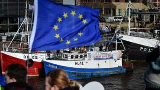 Anti-Brexit protestors fly an EU flag in front of a pro-Brexit campaign from fishermen in Newcastle.