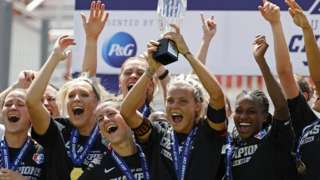 Rachel Daly lifts the trophy after winning the NWSL Challenge Cup Final with Houston Dash