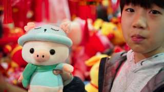 A boy holds a pig doll at a shopping mall