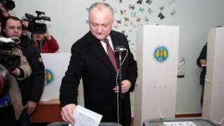 Igor Dodon, flanked by TV cameras, places his ballot paper into a ballot box