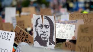 Protesters march holding placards and a portrait of George Floyd during a demonstration against racism and police brutality, in Hollywood, California on June 7, 2020