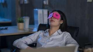 Mulher sentada em cadeira de escritório, reclinada, com papéis em cima seus olhos - indicando que ela está cansada