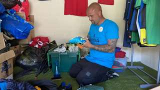 Luke Riggs cleans up a pair of donated football boots