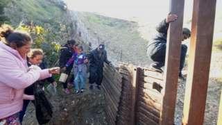 Honduran migrants climb over the U.S.-Mexico border fence
