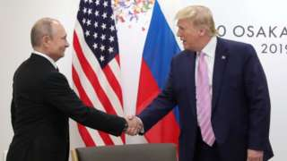 Russia's President Vladimir Putin shakes hands with US President Donald Trump