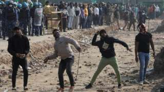 People who were shouting anti-farmers slogans throw stones, at a site of the protest against farm laws at Singhu border near New Delhi, India January 29, 2021.