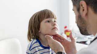 Child having tonsils checked by doctor.