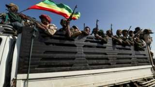Members of Amhara region militias ride on their truck as they head to face the Tigray People's Liberation Front (TPLF)