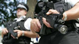 Two armed police officers patrol the streets around Whitehall, central London
