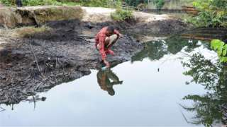 A man scoops spilled crude oil allegedly caused by Shell equipment failure floating at the bank of B-Dere waterways in Ogoniland, Rivers State, on August 11, 2011.