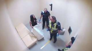 Tanya Day stands in a cell with police officers