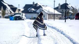 A man walks to his friend's home in a neighbourhood without electricity as snow covers the BlackHawk neighbourhood in Pflugerville, Texas, 15 February 2021