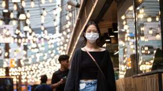 A woman wearing a protective face mask near World Square Sydney, Australia, 18 December 2020