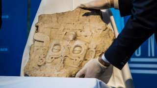 Unesco staff members place the Mayan stela on a display before the handover ceremony