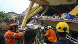 Rescue workers amid rubble