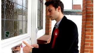 Josh Abey posting campaign leaflets through a door