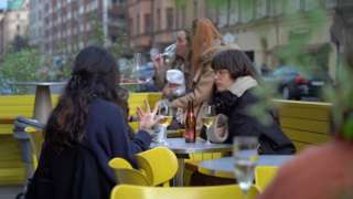 Young women drink and socialise in an outdoor seating area of a bar