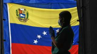 A staff member of Doctors Without Borders prepares herself waits for patients to be tested for COVId-19 in front of a Venezuelan flag at the Perez de Leon Hospital os the Petare neighbourhood, in eastern Caracas on June 23, 2020, amid the new coronavirus pandemic.